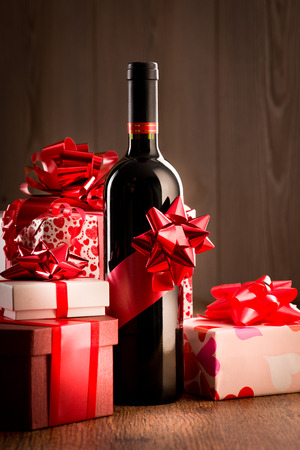 Wine bottle gift with red ribbon and colorful christmas gift boxes on wooden table. Stock Photo