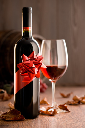 fallen fruit: Wine bottle with ribbon gift, wineglass with red wine and barrel on background. Stock Photo