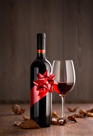 ワインボトル ギフト赤ワイングラス、紅葉の背景に木製の表面と。
