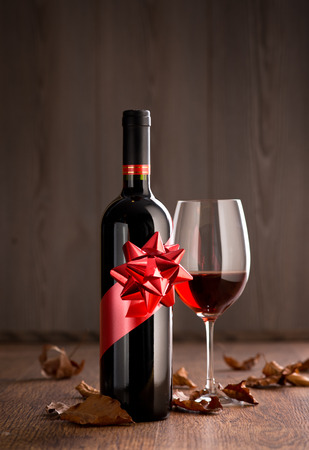 Wine bottle gift with red wine glass, autumn leaves and wooden surface on background. photo