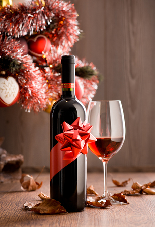 Wine bottle gift and wine glass filled with red wine, christmas tree and dry leaves on background. photo