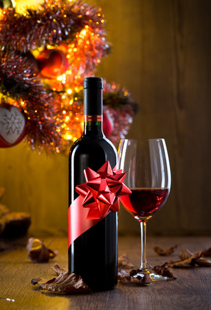 Wine bottle gift and wine glass filled with red wine, christmas tree and dry leaves on background. Stock Photo
