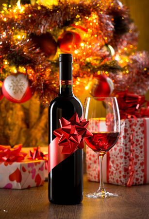 Wine bottle gift and wine glass filled with red wine, christmas gift boxes and tree on background. photo