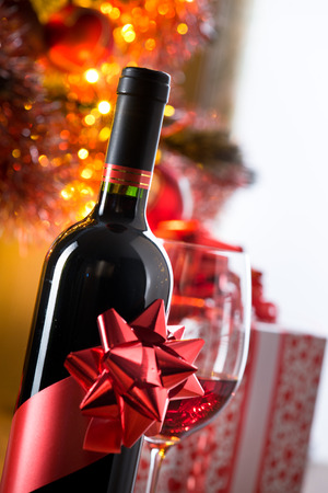 Wine bottle with ribbon and filled wineglass, christmas tree and gift boxes on background. Stock Photo