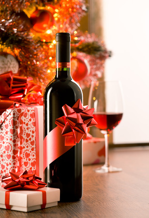 Wine bottle with red ribbon with christmas gift boxes and tree on background. photo