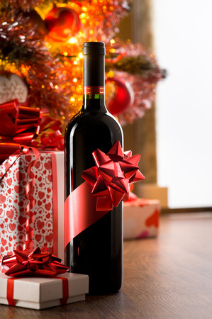 Wine bottle with red ribbon with christmas gift boxes and tree on background.