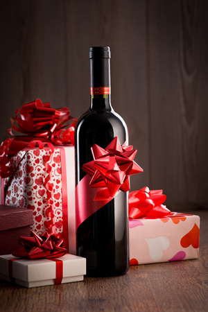 Wine bottle gift with red ribbon and colorful christmas gift boxes on wooden table. photo