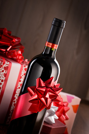 Wine bottle gift with red ribbon and gift boxes on wooden background. photo