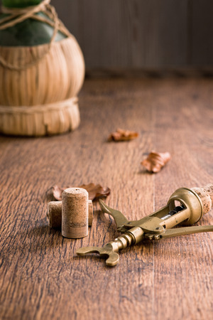 fiasco: Vintage corkscrew with corks, fallen leaves and fiasco bottle on background.