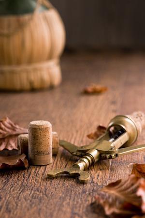 fiasco: Vintage corkscrew with corks, fallen leaves and fiasco bottle on background.