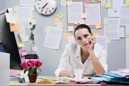messy office: Tired frustrated female office worker at desk looking at camera. Stock Photo