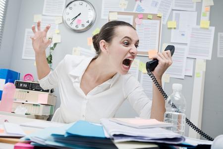 Angry gewezen zakenvrouw op de telefoon schreeuwen hardop. Stockfoto