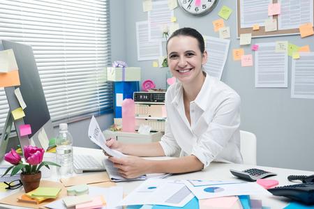 oficinista: Cuello blanco femenino alegre en escritorio de oficina leyendo una buena noticia en el periódico financiero.