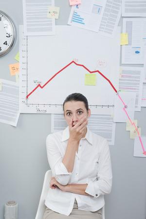 crisis economica: Conmocionado empresaria en el cargo en virtud de un gráfico de negocio negativa en la pared.