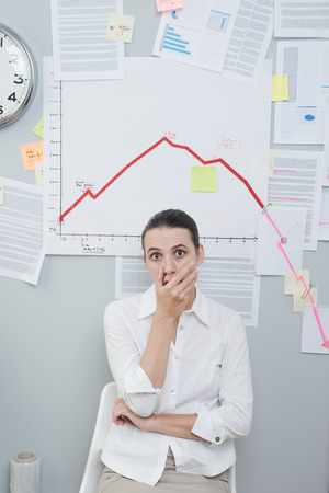 Shocked businesswoman in office under a negative business chart on the wall. photo