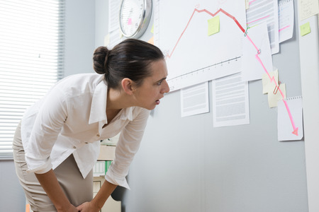 bent over: Stunned businesswoman checking a financial business chart on office wall with arrow going down.