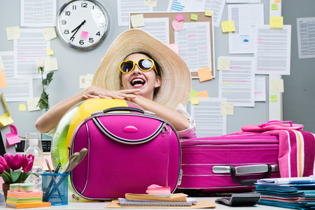 Cheerful office worker with pink luggage and sunglasses ready for vacations.