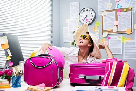 Glimlachend vrouwelijke beambte klaar om te vertrekken voor een vakantie met roze bagage. Stockfoto