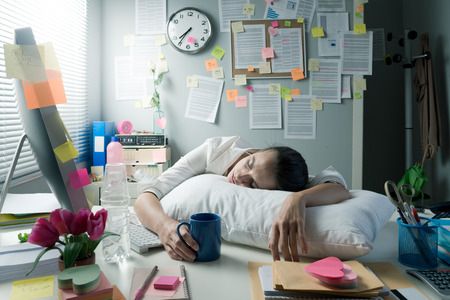 Tired businesswoman at office desk waking up with pillow and coffee. Фото со стока - 33142650