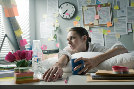 Overworked office woman with pillow working at computer.