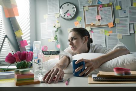 Surmené femme de bureau avec oreiller de travail à l'ordinateur. Banque d'images