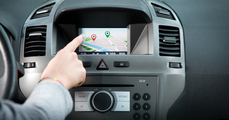sat: Female finger touching a touch screen navigation panel on car dashboard.