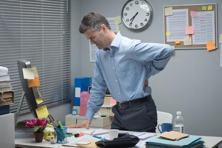 espalda: �Cansado de negocios que se inclina a su escritorio y tocando su espalda baja dolorosa.