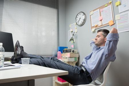 게으른 회사원 피트는 그의 작은 사무실에서 휴식. 스톡 콘텐츠