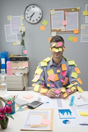 over burdened: Busy white collar sitting at desk covered with stick notes.