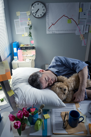 Funny office worker sleeping in the office overnight with teddy bear. photo
