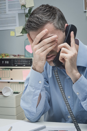 over burdened: Stressed employee on the phone touching his forehead. Stock Photo