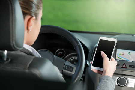 Young female driver using touch screen smartphone and gps navigation in a car.