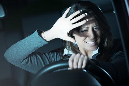 Doodsbang jonge vrouw rijden en het hebben van een auto-ongeluk in de nacht. Stockfoto