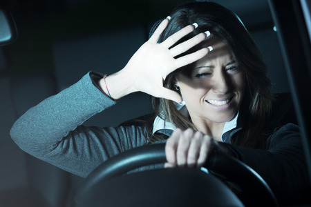 car safety: Young terrified woman driving and having a car accident at night. Stock Photo