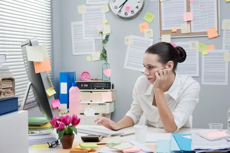 Bored gefrustreerde vrouwelijke beambte het werken op de computer met de hand op de kin.