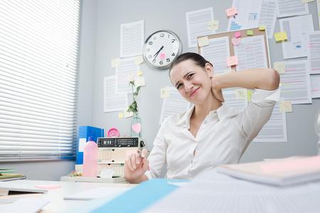collarin: Cuello blanco femenino cansado con rigidez en el cuello trabaja en el escritorio.