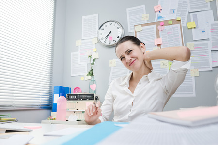 Tired female white collar with stiff neck working at desk.