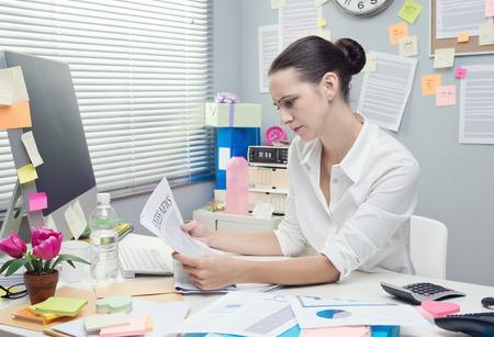 oficina desordenada: Empresaria seria en el escritorio de oficina leyendo un periódico financiero.