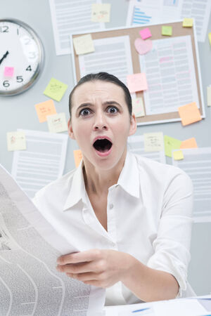 Shocked businesswoman mouth open reading bad news and looking at camera. photo
