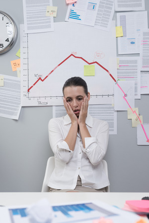 Depressed businesswoman under a negative business chart with arrow going down. photo