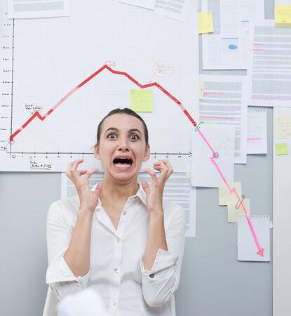 D'affaires choqué crier sous schéma financier négatif avec la flèche de descendre.