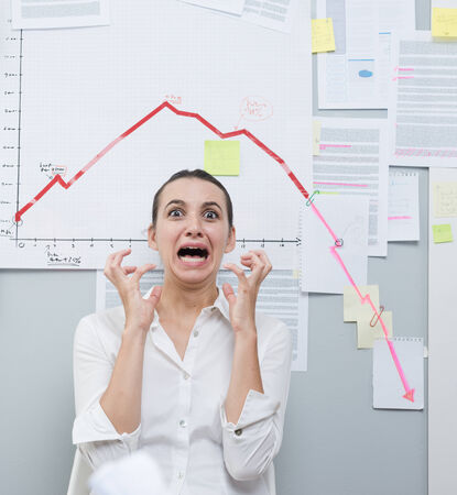 over burdened: Shocked businesswoman screaming under financial negative diagram with arrow going down. Stock Photo