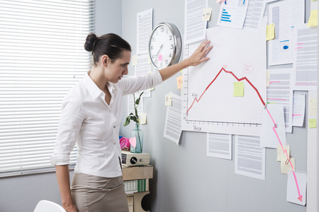 going down: Office worker analyzing a financial chart on office wall with arrow going down. Stock Photo