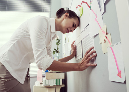 bent over: Female office worker bent over with head lening to a wall and negative business chart. Stock Photo