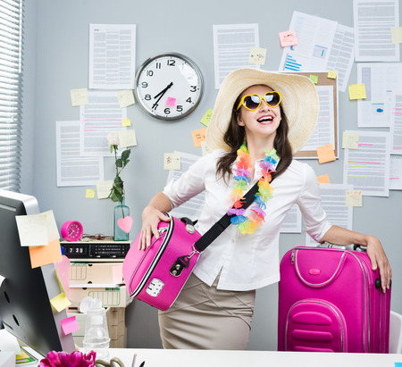 Smiling female office worker ready to leave for vacations with pink luggage.