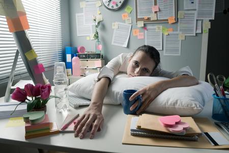 oficina desordenada: Empresaria cansada en la oficina escritorio despertar con almohada y café. Foto de archivo