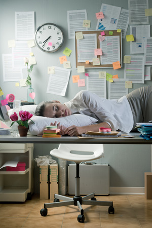 Tired businesswoman sleeping in office overnight with pillow on desk. photo