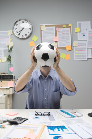 inattentive: Businessman in his office holding a soccer ball in front of his face.