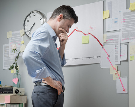 downwards: Concerned businessman at work looking at negative business chart with arrow going downwards. Stock Photo
