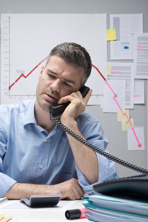 Consultant on the phone with negative business chart on background. photo